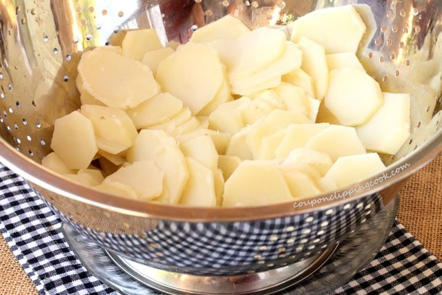 Sliced cooked potatoes in colander