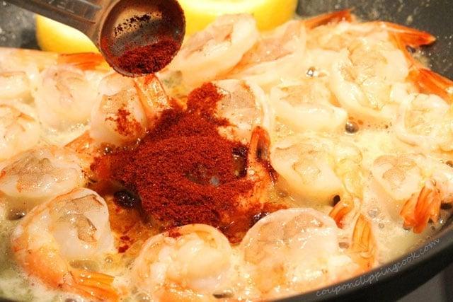 Add paprika to shrimp in skillet