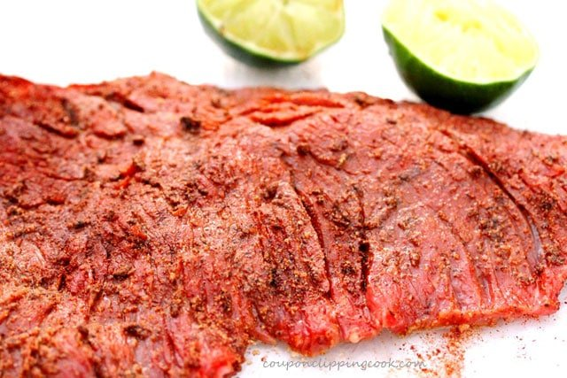 Seasoned flap meat and lime on plate