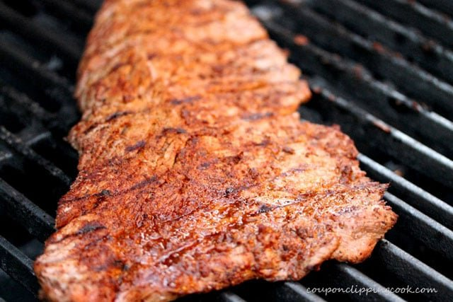 Seasoned flap meat on barbecue grill