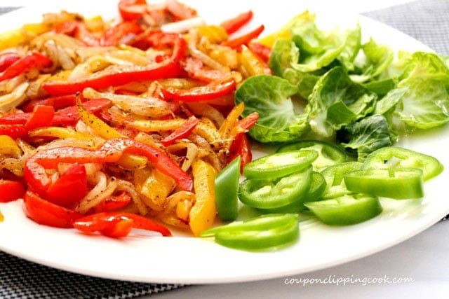 Cooked bell pepper slices with vegetables on plate