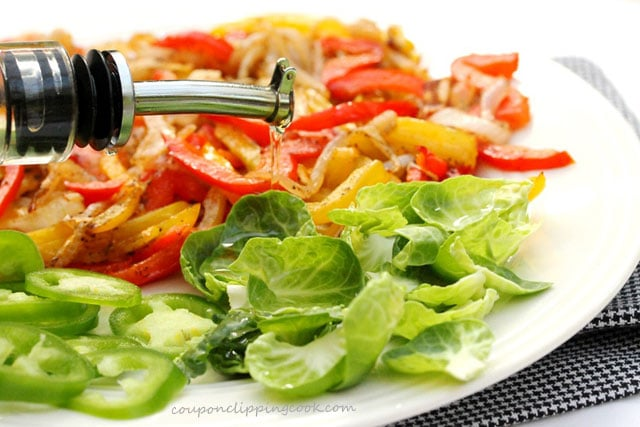 Pour olive oil on vegetables on plate
