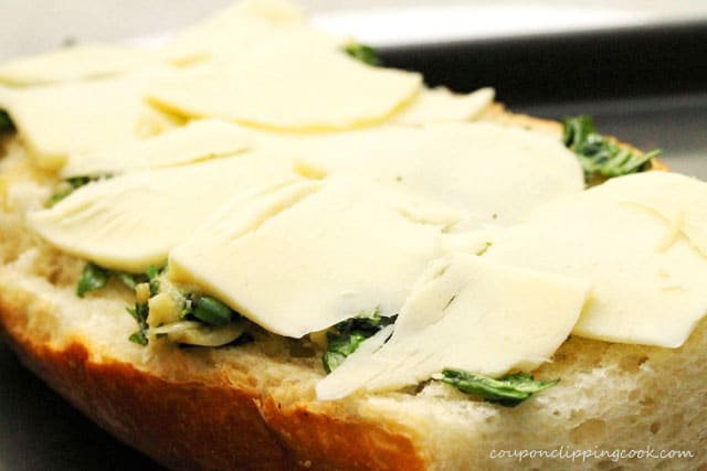 Sliced cheese on top of herb French bread