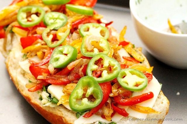 Sliced jalapenos and vegetables on top of French Bread