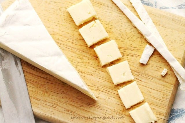 Cut brie cheese on cutting board
