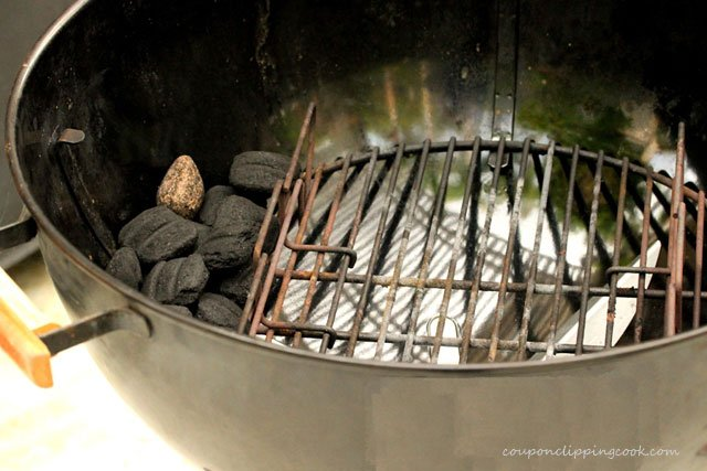 Adding coals to kettle barbecue