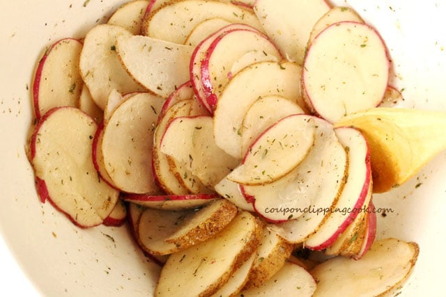 Sliced potatoes in bowl with herbs