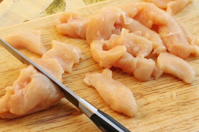 Cut raw chicken on cutting board