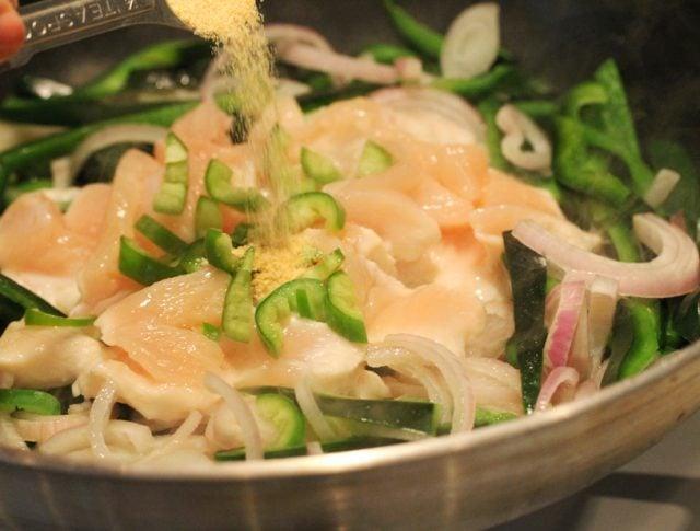 Add garlic powder to chicken in pan