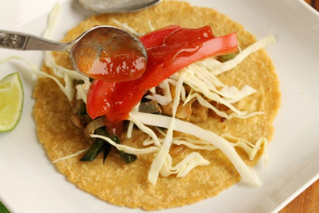Add salsa in taco on plate