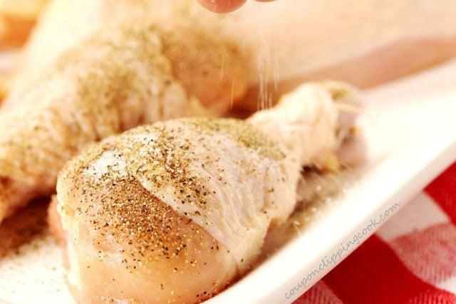 Add salt to raw chicken on plate