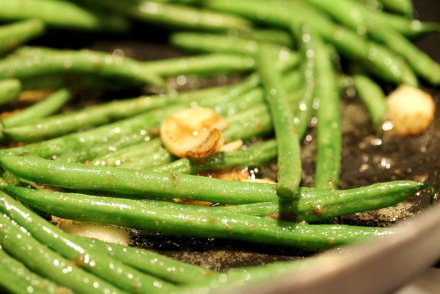 Cook garlic and green beans in pan