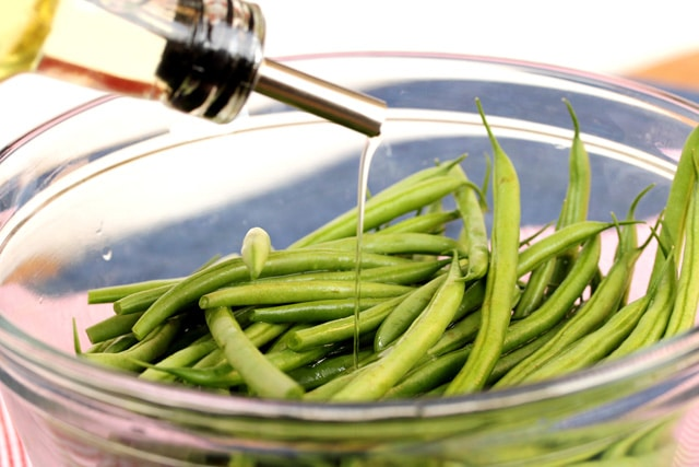 Add olive oil to green beans in bowl