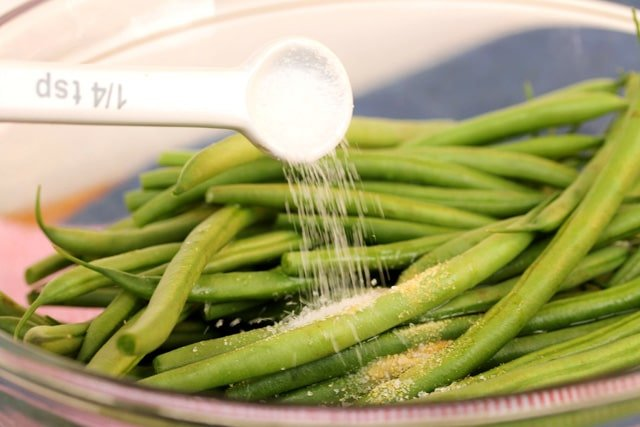 Add salt on green beans in bowl