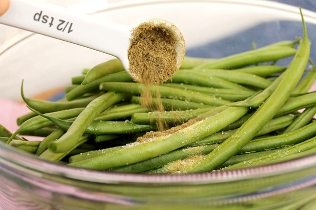 Add sage on green beans in bowl