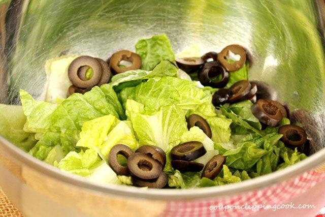 Sliced black olives with lettuce in bowl