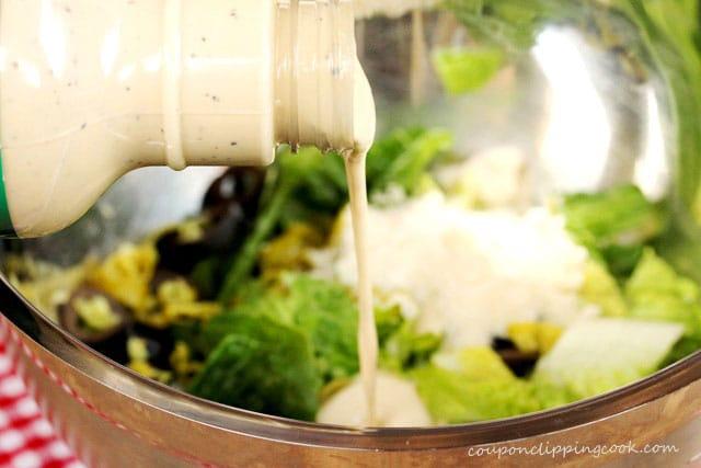 Add Caesar dressing on salad in bowl