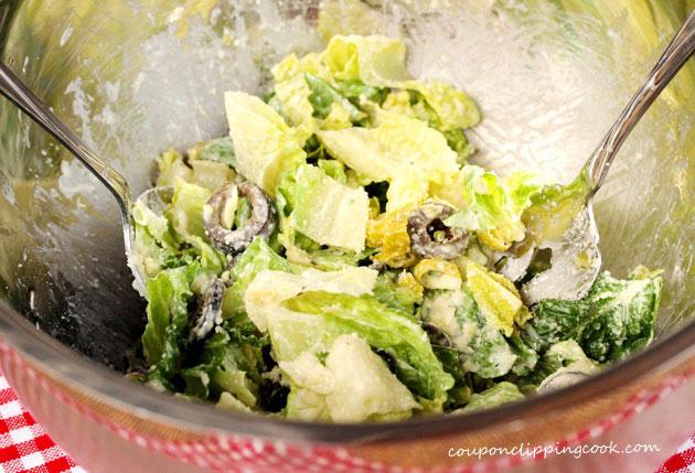 Toss Caesar salad in bowl