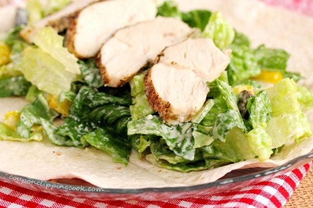 Sliced chicken and salad on tortilla
