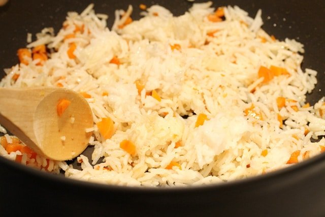 Stir rice and carrots in skillet