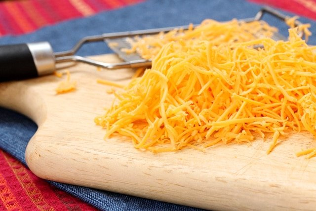 Shred cheese on cutting board