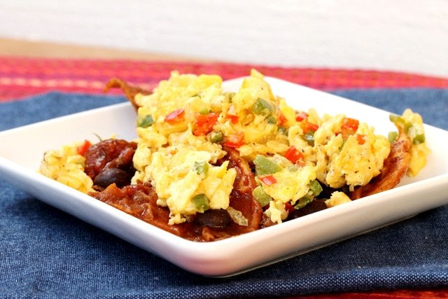 Scrambled eggs, chili and tortilla chips on plate