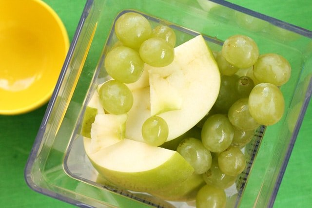 Green grapes and apples in blender jar