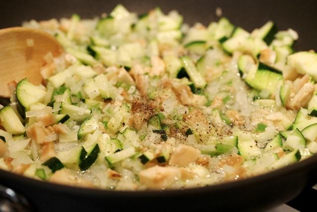 Season chopped vegetables in pan