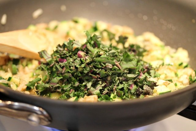Chopped kale in skillet with vegetables