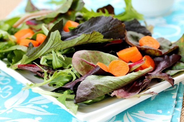 Mixed greens with carrots on plate