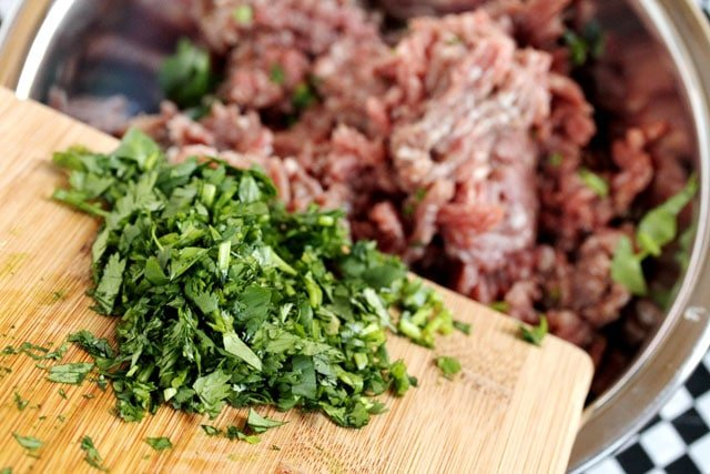 Add chopped cilantro to ground beef in bowl