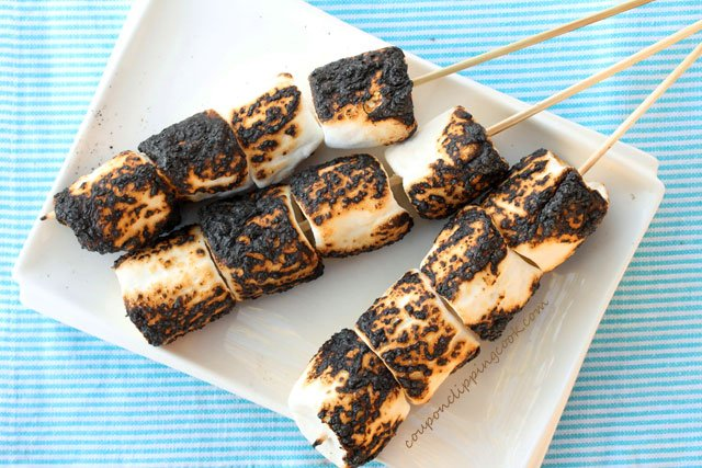 Toasted marshmallows on skewers on plate