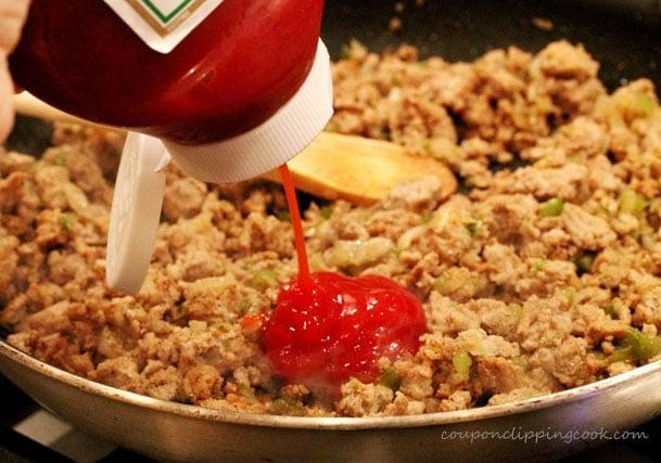 Add ketchup to ground turkey in skillet