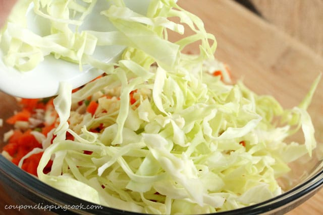 Add sliced green cabbage to bowl