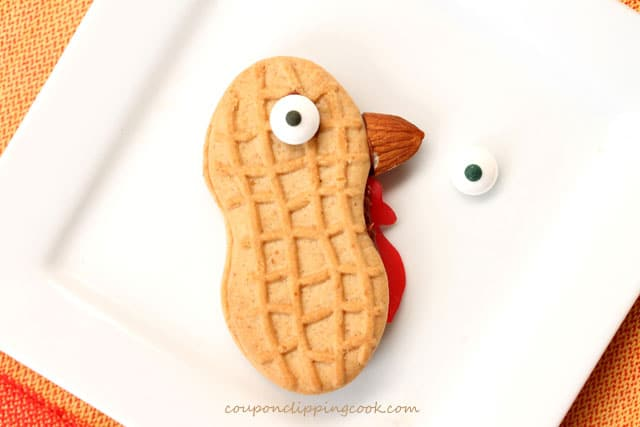 Add candy eye balls on Nutter Butter cookie with almond