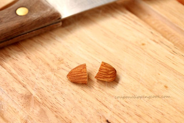 Cut whole almond in half on cutting board