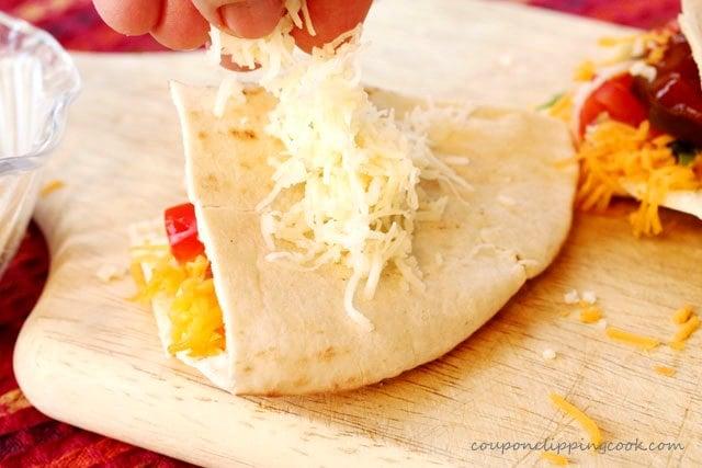 Add cheese on top of Pita Quesadillas
