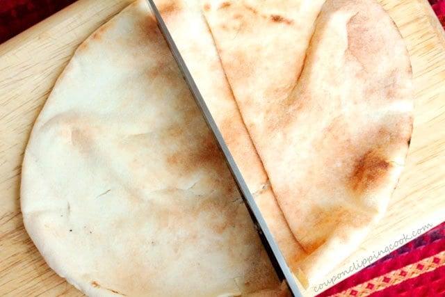 Cut pita pocket bread in half on cutting board