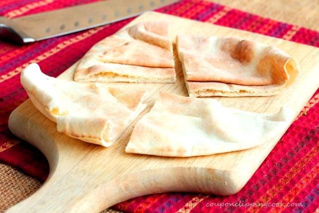 Cut pita pocket bread in quarters