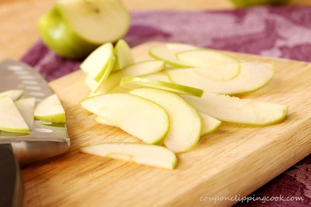 Sliced green apples on cutting board