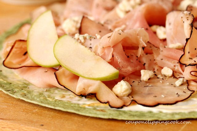 Add sliced green apples on ham on tortilla
