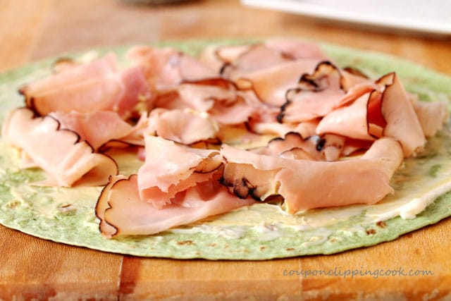Add sliced ham on green tortilla wrap