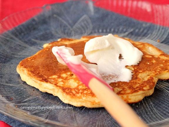 Spread yogurt on pancake on plate