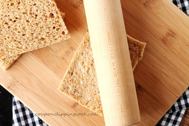 Flatten sandwich bread with rolling pin on board