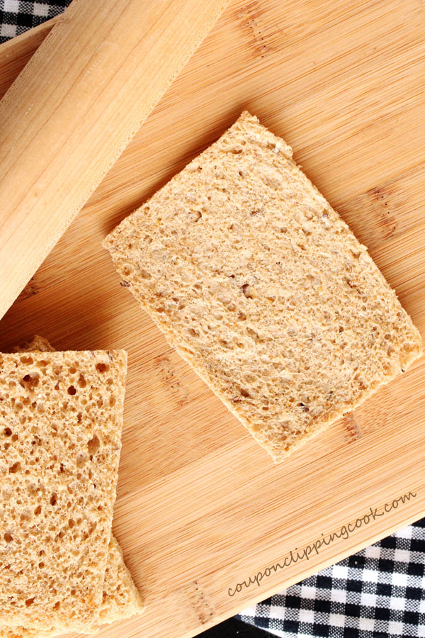 Flattened sandwich bread on cutting board