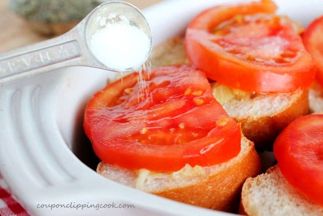 Add salt on tomatoes on roasted garlic bread