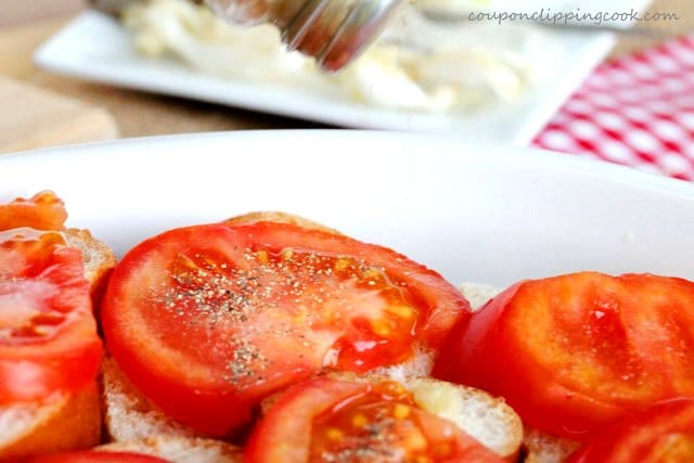 Add pepper on sliced tomatoes on roasted garlic bread