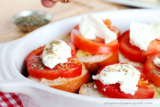 Top tomatoes and cheese with dried oregano