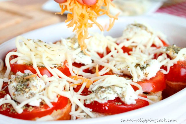 Add shredded cheese on top of sliced tomatoes