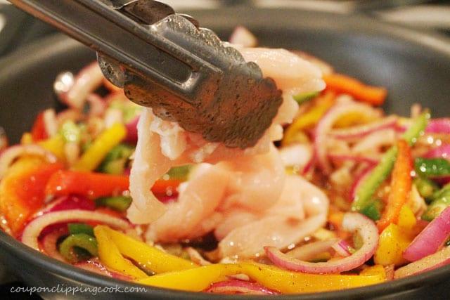 Add chicken to fajita vegetables in pan